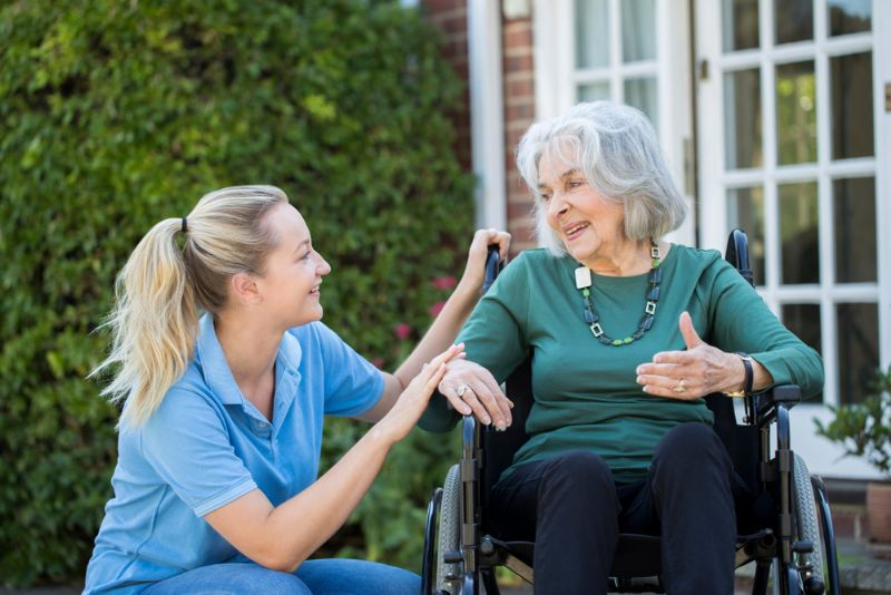 Happy care worker crouching down to talk to service user in wheelchair